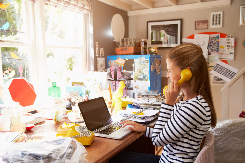 a-woman-on-the-phone-at-a-cluttered-desk-at-home-000064637879_small
